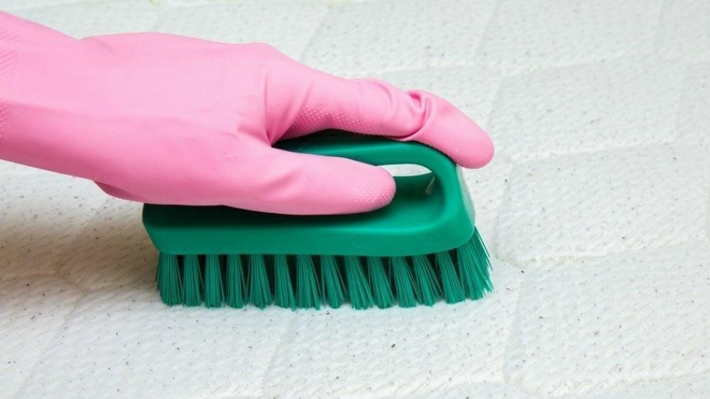 un cepillo suave y jabón neutro para eliminar manchas de los colchones